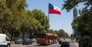 SANTIAGO DE CHILE, CHILE - JANUARY 26, 2018: Intense traffic on Avenida La Alameda, the most important street in Santiago de Chile. In the background, the flag of Citizenship Square