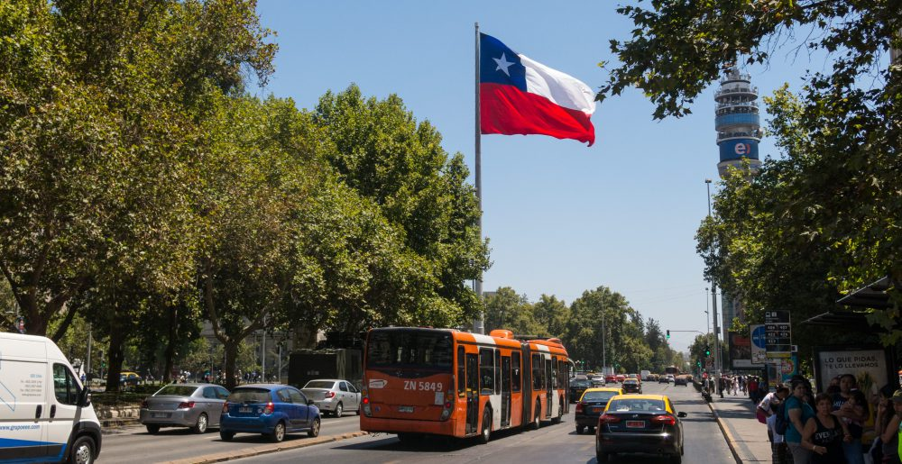 SANTIAGO DE CHILE, CHILE - JANUARY 26, 2018: Intense traffic on Avenida La Alameda, the most important street in Santiago de Chile. In the background, the flag of Citizenship Square