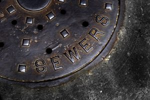 Man hole cover for sewer entry with iron grate on street in a city